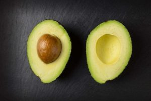 an avocado cut in half showcasing one important component of a healthy diet for men over 40